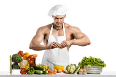 Man bodybuilder in white toque blanche and cook protective apron Royalty Free Stock Image