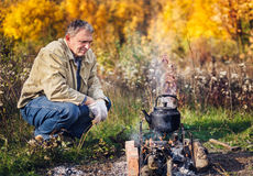 Man boils sooty kettle on the fire. Man boils sooty kettle on the campfire, autumn Royalty Free Stock Photography