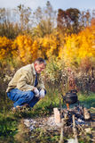 Man boils sooty kettle on the fire. Man boils sooty kettle on the campfire, autumn Stock Photography
