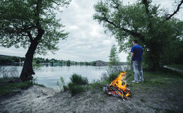Man and bonfire in the spring forest. coals of fire Stock Image