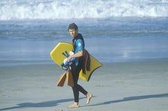 Man with boogie board. Walking on beach, Laguna, CA Stock Photos