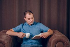 Man with a book and a coffee cup in his hands sitting in an armchair and reading. Psychologist royalty free stock images