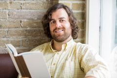 Man With Book In Coffeeshop Royalty Free Stock Photo