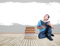 Man With Book Concept,Reading Imagination. Asian Man Sitting Indoors With Books And Wall Painting For Text And Ideas Stock Image