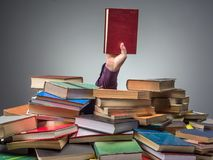 Man with book found among pile of books. Male hand protruding from pile of books holding the book he was looking for Royalty Free Stock Images