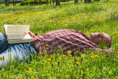 Man with book on a meadow Stock Photography
