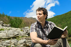 Man and book in nature. Man holds a book in enjoys his freedom in natural landscape Stock Photos