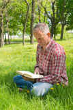 Man with a book in the park Royalty Free Stock Image