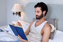 Man book relaxing bed Stock Images