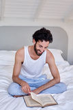 Man book relaxing bed Royalty Free Stock Images