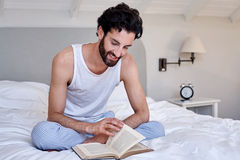Man book relaxing bed Stock Image