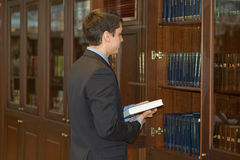 Man and a book shelves. Office thoughts stock photo