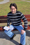 Man with book sitting on a bench Stock Images