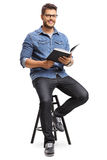 Man with a book sitting on a chair Royalty Free Stock Image