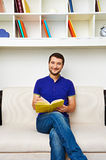 Man with book sitting on the sofa Stock Photo