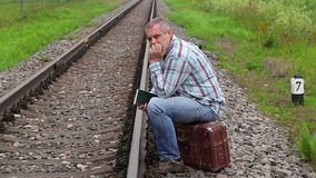 Man with book sitting on suitcase near railway. In summer day stock video