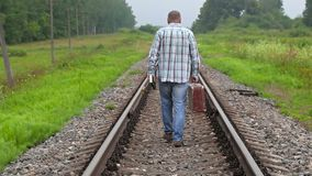 Man with book and suitcase walking away on railway. In summer day stock video