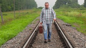 Man with book and suitcase walking on railway. In summer day stock video