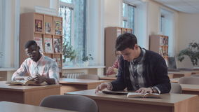 Man with book and tablet looking in library stock video