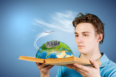 Man with book. Young man in casual holding opened book with city model. Elements of this image are furnished by NASA Stock Image