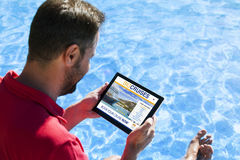 Man booking cruise travel by internet with a tablet at the swimm Stock Photos