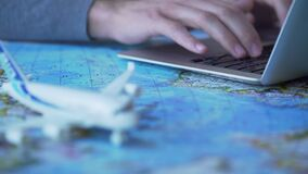 Man booking flight for business trip, typing on laptop, airplane model on map. Stock footage stock footage