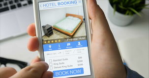 Man booking hotel suit using his smartphone and online booking mobile app sitting at his desk stock video footage