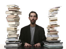 Man and books. Sitting man with a lot of book on the table royalty free stock image