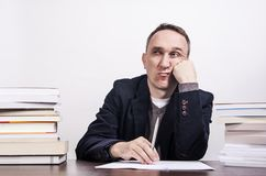 Man with books on desk struggle with writing on white background. Office worker overloaded with paperwork. Many books on desk. Man struggle with writing on white Stock Photo