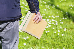 Man with books on green meadow Royalty Free Stock Photos