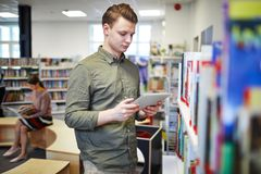 Man in bookshop. Young serious man with tablet browsing in the net while standing by bookshelf in library or bookshop stock photo