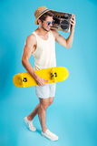 Man with boombox walking and holding skateboard. Happy young man with boombox walking and holding skateboard Stock Images