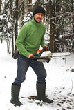 Man in boots and a chainsaw in the woods with a fierce facial ex Royalty Free Stock Image