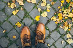 Man boots top view with yellow leaves Royalty Free Stock Photos