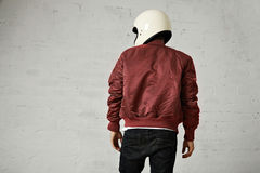 Man in a bordeaux pilot jacket with helmet Royalty Free Stock Photography