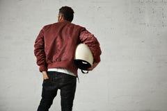 Man in a bordeaux pilot jacket with helmet Royalty Free Stock Photos