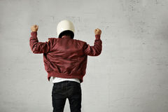 Man in a bordeaux pilot jacket with helmet. Man in white motorcycle helmet and burgundy pilot jacket shot from the back with both fists up in the air with shaka Royalty Free Stock Images