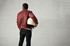 Man in a bordeaux pilot jacket with helmet Stock Photography