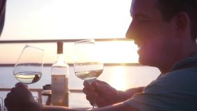 A man is bored in a cafe, holds two cradles in his hands and checks himself with himself, against the backdrop of the. Sea and a beautiful sunset stock footage