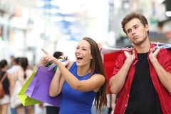Man bored shopping with his girlfriend. Bored men shopping with his girlfriend in a commercial street Royalty Free Stock Images
