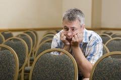 Man at a boring conference. Man sitting alone at a boring conference Royalty Free Stock Photography