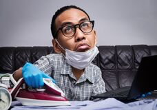 Man with boring face working with very busy business and housework part, ironing, working with laptop during self isolation