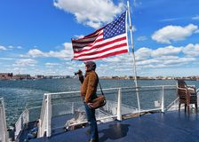Man at Boston waterfront and United States national flag MA stock image