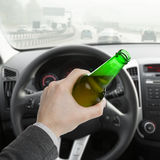 Man with bottle of beer while driving car - 1 to 1 ratio Stock Photos