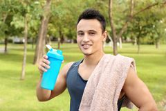 Man with bottle of protein shake. In green park stock photography