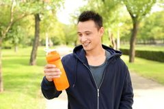 Man with bottle of protein shake. In green park stock photos