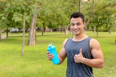 Man with bottle of protein shake in park. Space for text royalty free stock images