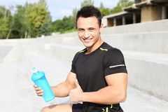Man with bottle of protein shake. On street stock image