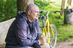 Man with bottle of water on bench near bicycle Royalty Free Stock Images
