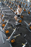 Man with bottle of water on exercise bicycle in gym, using towel, elevated view Stock Photography